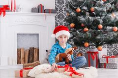 Gullig lycklig pojke i den santa hatten med leksakjulgåvor Royaltyfri Bild