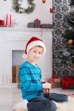 Gullig lycklig pojke i den santa hatten med leksakjulgåvor Fotografering för Bildbyråer