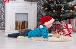 Gullig lycklig pojke i den santa hatten med leksakjulgåvor Royaltyfria Bilder