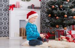Gullig lycklig pojke i den santa hatten med leksakjulgåvor Royaltyfri Foto