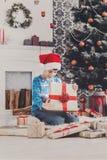 Gullig lycklig pojke i den santa hatten som packar upp julgåvor Royaltyfri Bild