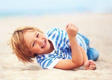 Gullig lycklig skratta pojke, unge som har gyckel på den sandiga stranden, sommarsemester Arkivfoton
