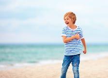 Gullig lycklig skratta pojke, unge som har gyckel på den sandiga stranden, sommarsemester Fotografering för Bildbyråer