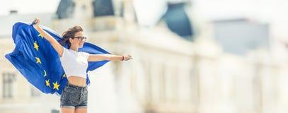 Gullig lycklig ung flicka med flaggan av den europeiska unionen framme av en historisk byggnad någonstans i Europa royaltyfri foto