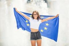 Gullig lycklig ung flicka med flaggan av den europeiska unionen framme av en historisk byggnad någonstans i Europa arkivbilder