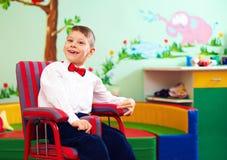 Gullig lycklig unge i rullstolen, bärande glade trasor i mitten för barn med speciala behov royaltyfri bild