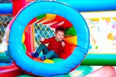 Gullig lycklig unge, pojke som spelar i uppblåsbar dragning på lekplats Arkivbild