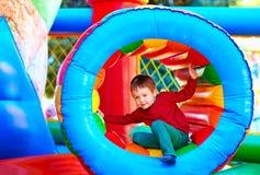 Gullig lycklig unge, pojke som spelar i uppblåsbar dragning på lekplats Fotografering för Bildbyråer