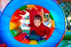 Gullig lycklig unge, pojke som spelar i uppblåsbar dragning på lekplats Royaltyfri Foto