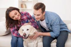 Gullig make och fru som vilar med husdjuret Royaltyfria Bilder