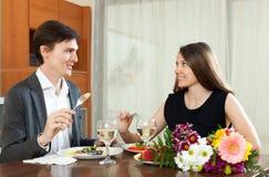 Gullig man och kvinna som har den romantiska matställen Arkivbilder