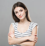 Gullig mjuk ren le posera grå bakgrund för härlig stående för ung kvinna Arkivbild