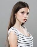 Gullig mjuk ren le posera grå bakgrund för härlig stående för ung kvinna Royaltyfria Foton