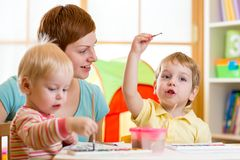 Gullig moder som undervisar hennes ungar att måla royaltyfri fotografi