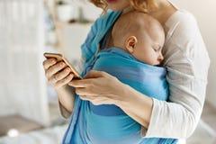 Gullig mycket liten unge som fridfullt ta sig en tupplur, medan modern som kramar honom och smsar maken vid telefonen som frågar  Arkivfoto
