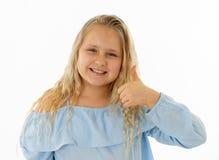Gullig n?tt flicka med den lyckliga framsidan och tummar upp gest I m?nskliga sinnesr?relser och uttryck arkivbilder