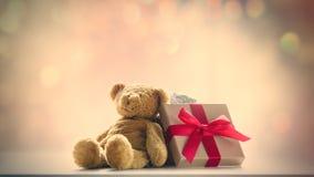 Gullig nallebjörn och härlig gåva på bokehbacen för felika ljus Fotografering för Bildbyråer