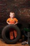 Gullig och rolig liten mekaniker med ett gummihjul fotografering för bildbyråer