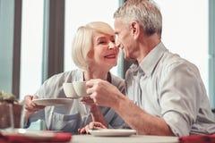 Gullig pensionerad man och kvinna som dricker kaffe arkivfoton
