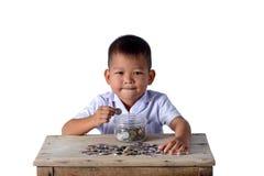 Gullig pojke för asiatiskt land som sätter mynt in i den isolerade exponeringsglasbunken på vit bakgrund arkivfoto