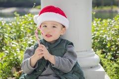 Gullig pojke för blandat lopp med den Santa Hat och godisrottingen Fotografering för Bildbyråer