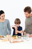 gullig pojke hans peppar som sätter salt sallad Arkivfoton