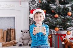Gullig pojke i den santa hatten som packar upp julgåvor Royaltyfri Foto