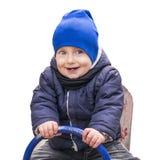 Gullig pojke i den varma kläderna som sitter på den isolerade sesågen på vit bakgrund Lyckligt barnsammanträde på gunga Fotografering för Bildbyråer