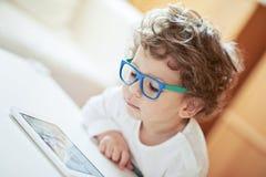 Gullig pojke i den vita t-skjortan, bärande exponeringsglas, hållande ögonen på saga - ljus bakgrund Älskvärd liten forskare Royaltyfria Foton