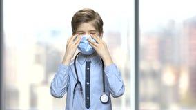 Gullig pojke i medicinsk maskering genom att använda stetoskopet stock video
