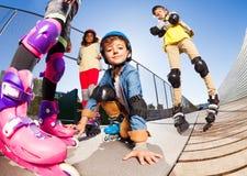 Gullig pojke i rullskridskor som har gyckel med vänner fotografering för bildbyråer