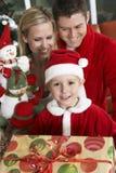 Gullig pojke i Santa Claus Outfit Holding Gifts With föräldrar bakom Arkivfoton