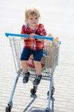 Gullig pojke i shoppingspårvagn Arkivbilder