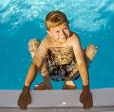 Gullig pojke i simbassänglaughes royaltyfria bilder