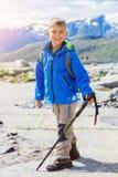 Gullig pojke med att fotvandra utrustning i bergen Royaltyfri Fotografi