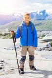 Gullig pojke med att fotvandra utrustning i bergen Arkivbilder
