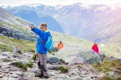 Gullig pojke med att fotvandra utrustning i bergen Royaltyfri Foto
