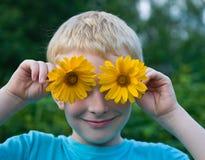 Gullig pojke med blommor på ögon som har gyckel Royaltyfria Foton