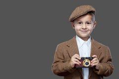 Gullig pojke med den gamla fotokameran royaltyfri bild