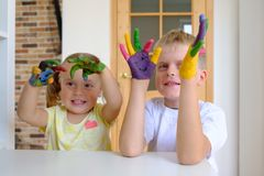 Gullig pojke med målade händer som spelar med hans hemmastadda lilla syster fotografering för bildbyråer