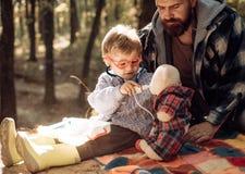 Gullig pojke med nästorkaren nära höstträd Fader- och barnsonen i h?st parkerar att ha gyckel och att skratta lycklig familj royaltyfri foto