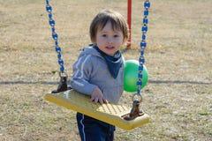 Gullig pojke med near gunga för boll Arkivfoto