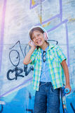 Gullig pojke med skateboarden utomhus och att stå på gatan med olika färgrika grafitti på väggarna Royaltyfri Bild