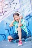 Gullig pojke med skateboarden utomhus och att stå på gatan med olika färgrika grafitti på väggarna Arkivfoton