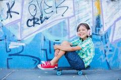 Gullig pojke med skateboarden utomhus och att stå på gatan med olika färgrika grafitti på väggarna Royaltyfri Foto