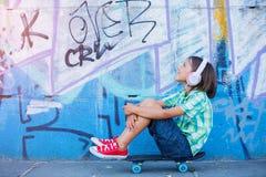 Gullig pojke med skateboarden utomhus och att stå på gatan med olika färgrika grafitti på väggarna Fotografering för Bildbyråer
