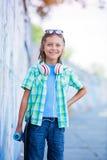 Gullig pojke med skateboarden utomhus och att stå på gatan med olika färgrika grafitti på väggarna Arkivfoto