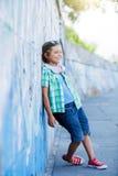 Gullig pojke med skateboarden utomhus och att stå på gatan med olika färgrika grafitti på väggarna Arkivbild