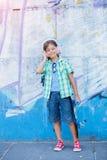 Gullig pojke med skateboarden utomhus och att stå på gatan med olika färgrika grafitti på väggarna Royaltyfri Fotografi