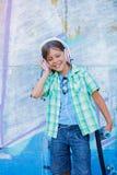 Gullig pojke med skateboarden utomhus och att stå på gatan med olika färgrika grafitti på väggarna Royaltyfria Bilder